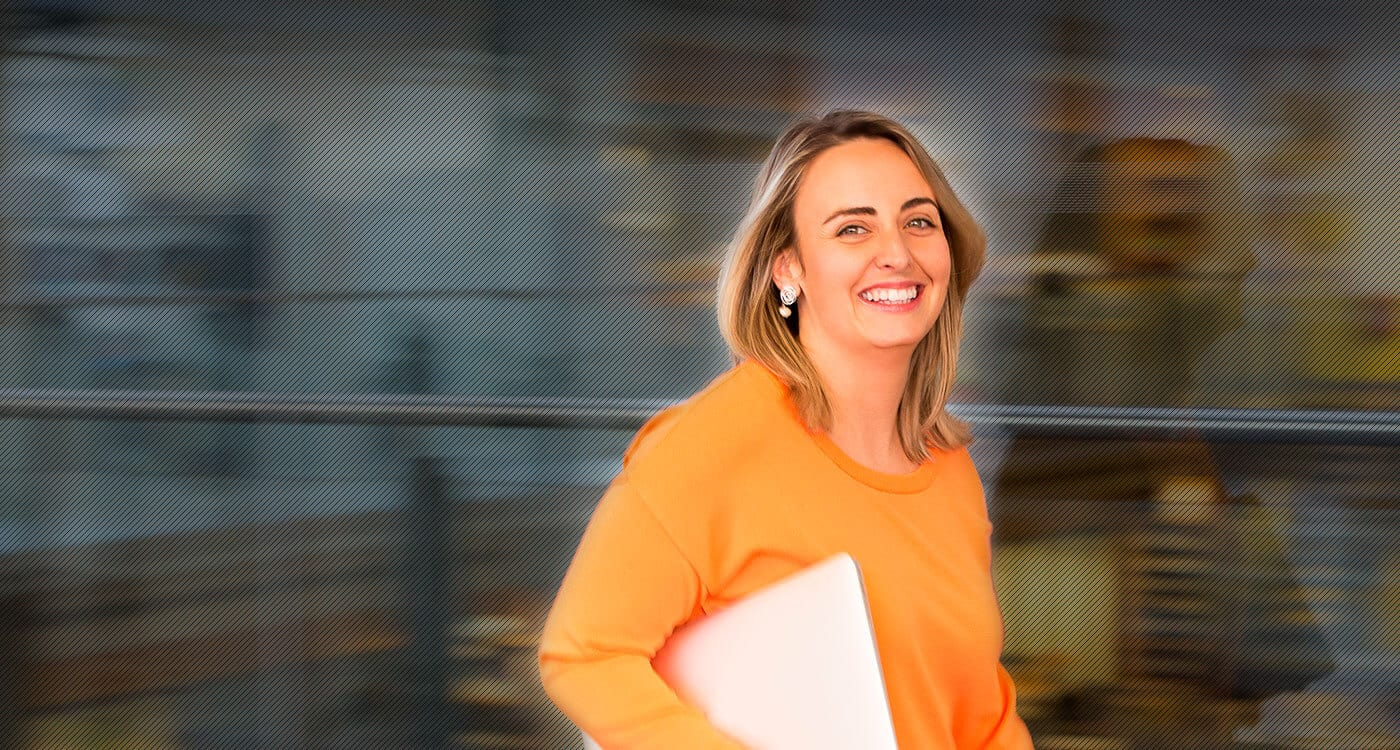 woman in orange top smiling at camera and holding laptop with background blurred
